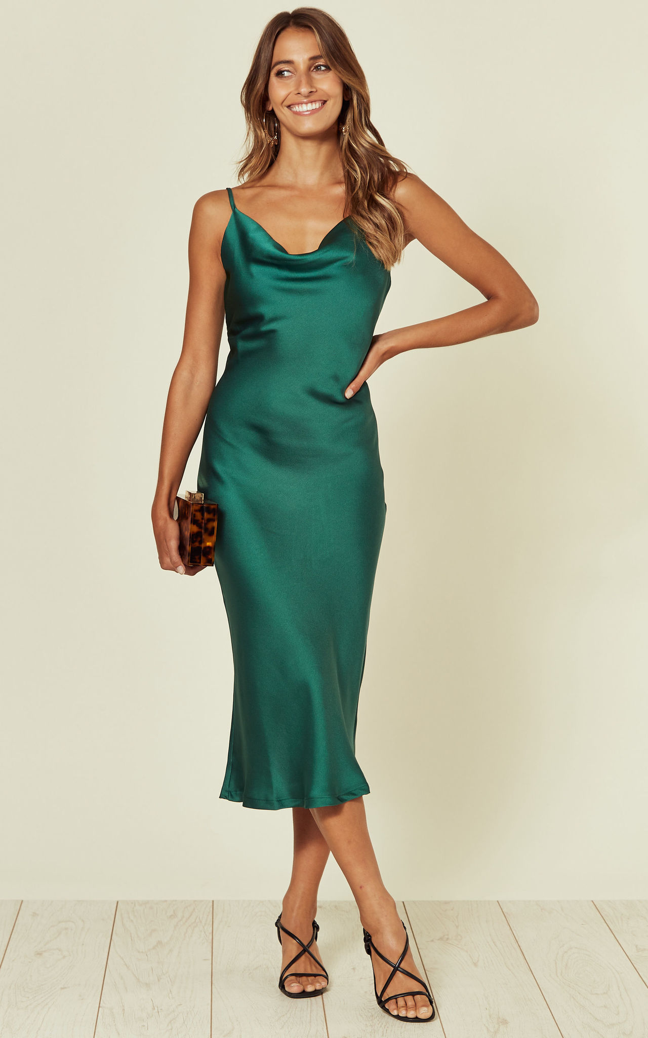 Model wears a green midi slip dress with cowl neck
