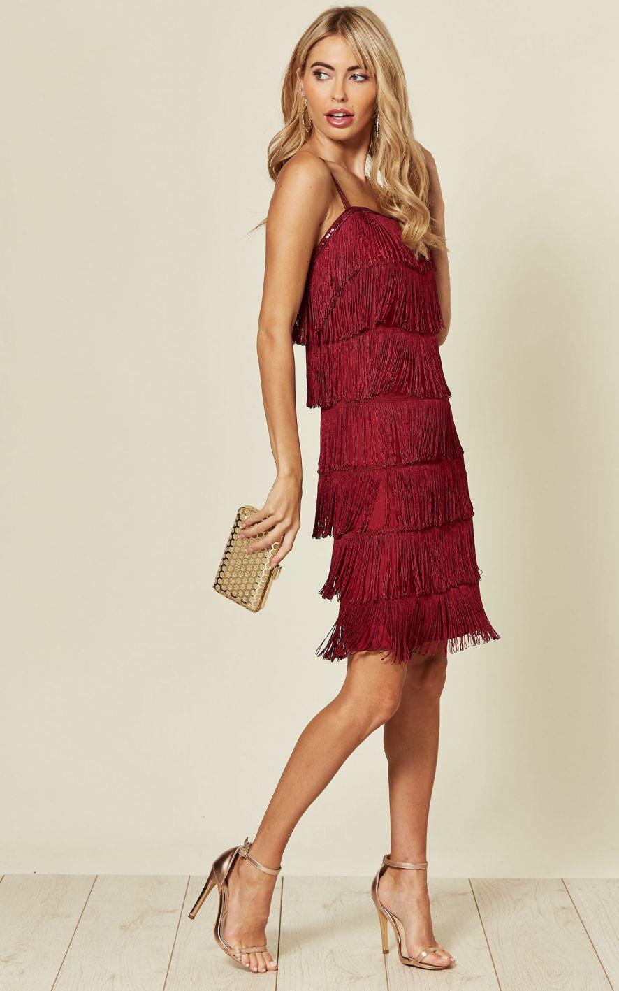 Model wears flapper style fringed mini dress in wine red