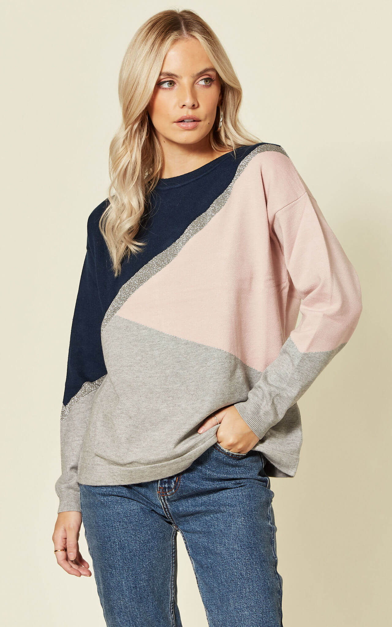 Model wears roxy knit colour block jumper with glittery detail with blue jeans