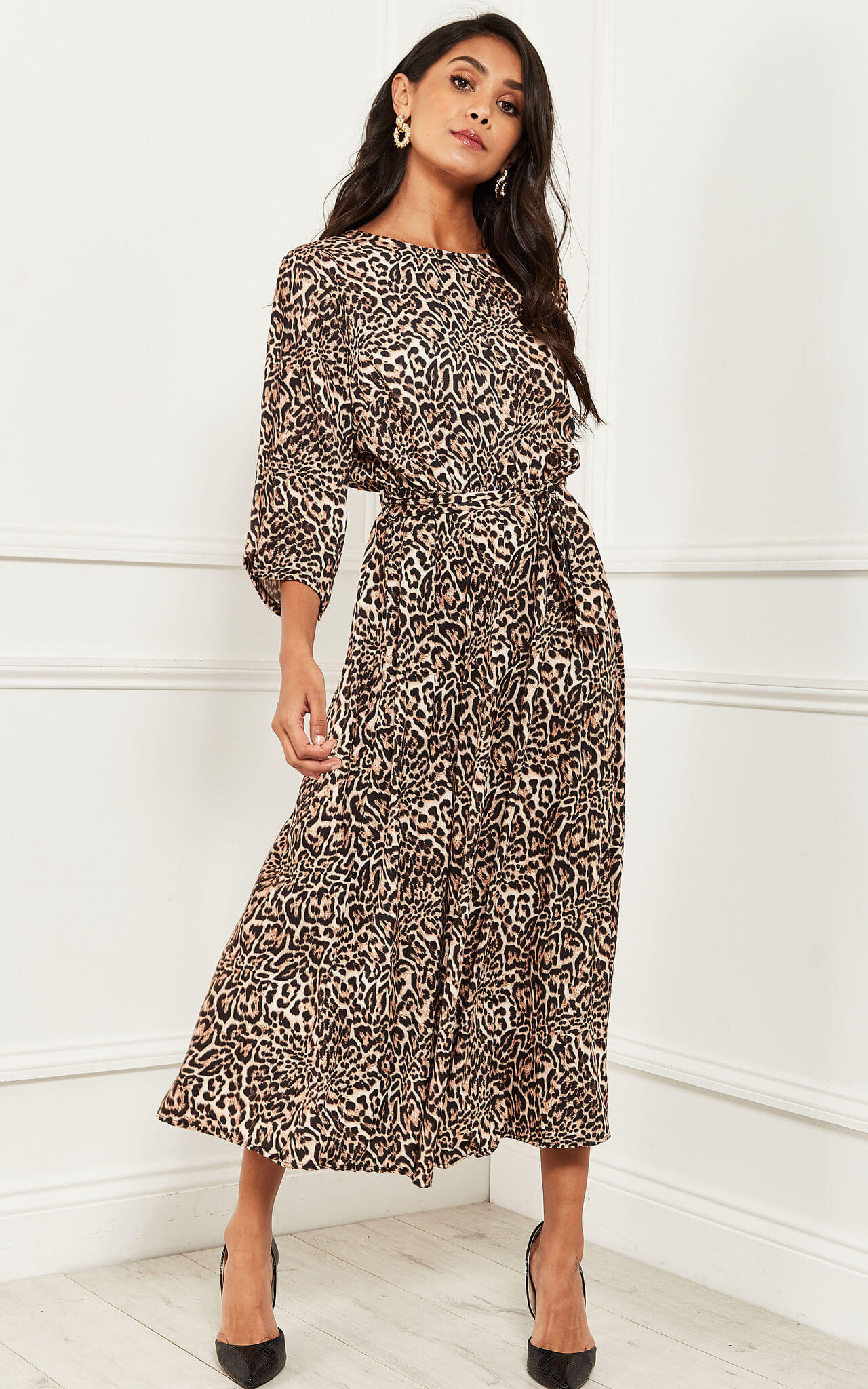 Model wears a leopard midaxi dress with 3/4 length sleeves and black heels