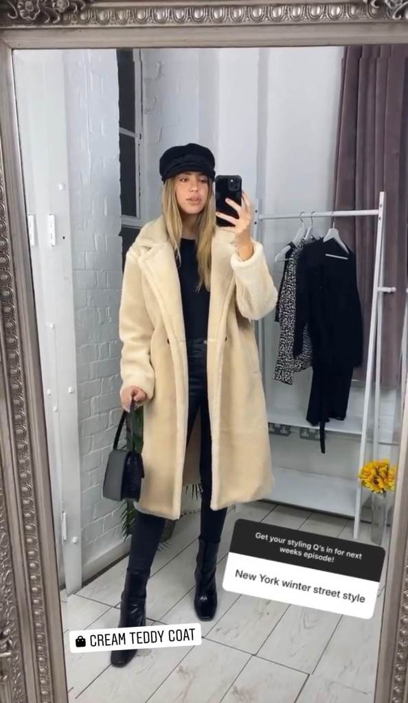 Model wears a cream teddy coat over a black outfit while taking a mirror selfie