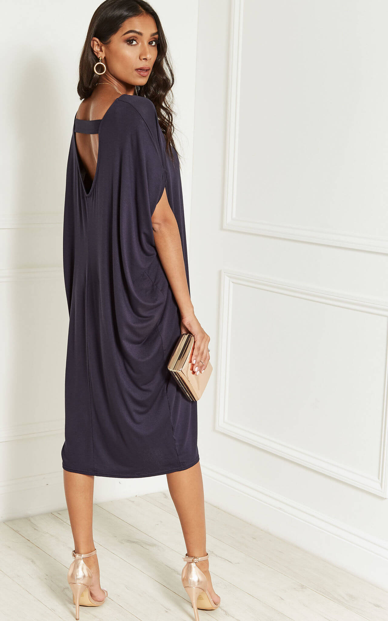Model wears navy scoop back dress in a slouchy fit with rose gold heels and a clutch bag