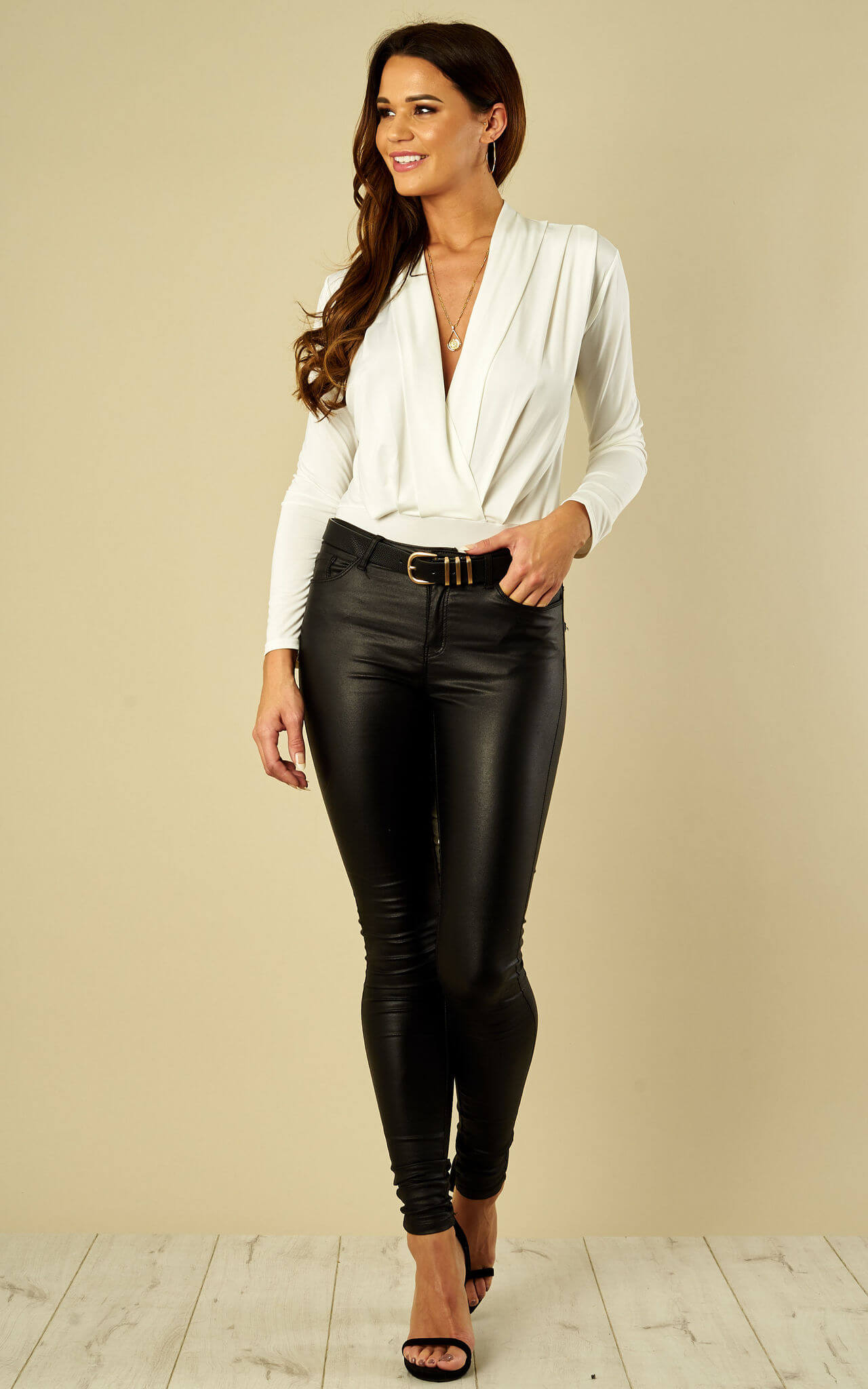 Model wears white wrap bodysuit with black coated jeans and barely there heels
