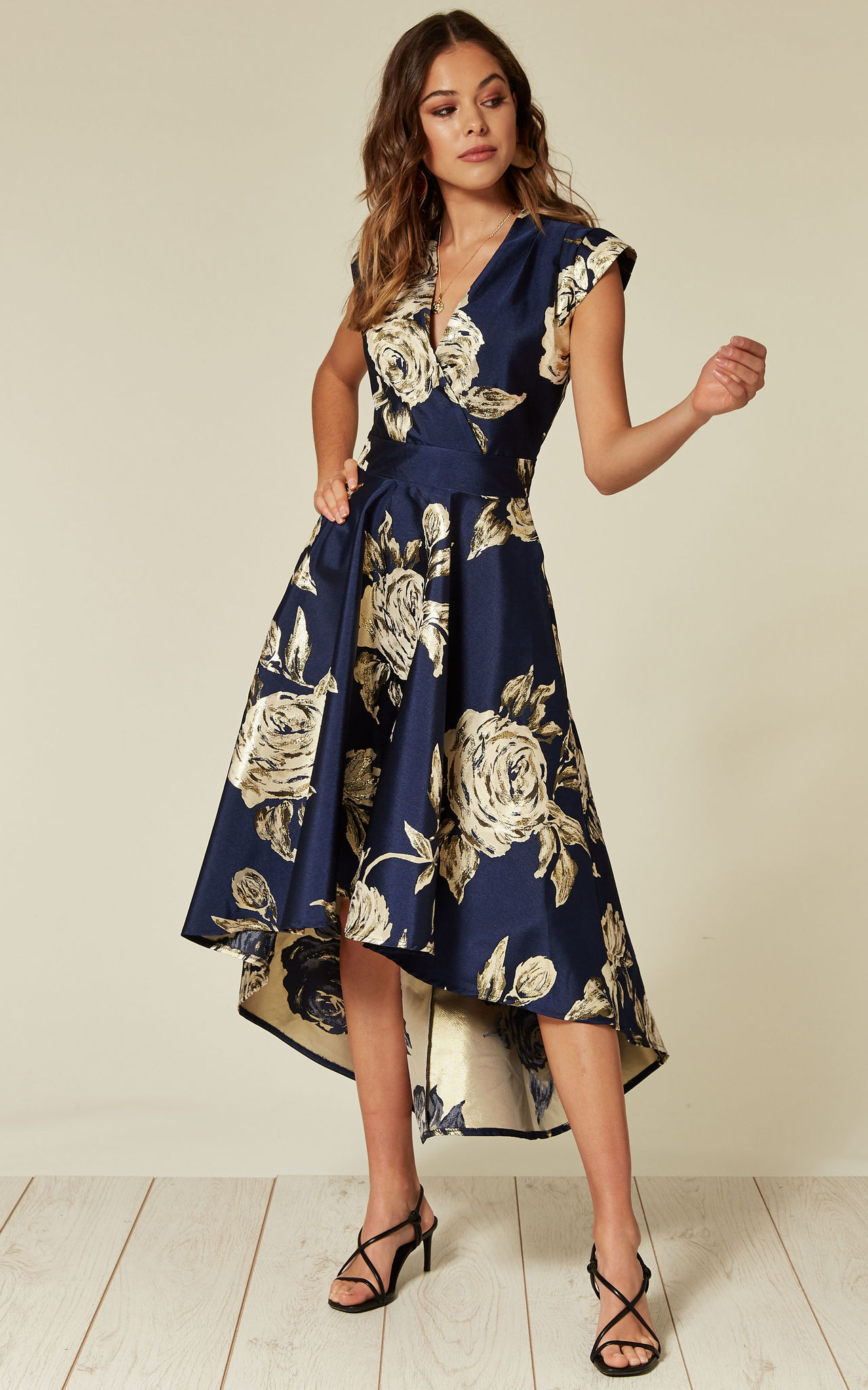 Model wears a navy floral satin high low dress with pockets