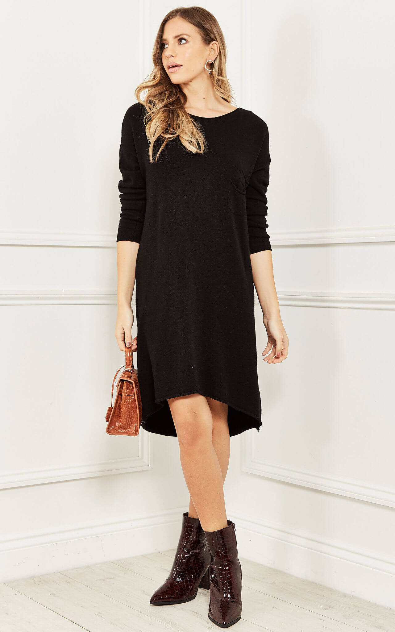 Model wears a black long sleeve knitted dress with pockets with brown ankle boots