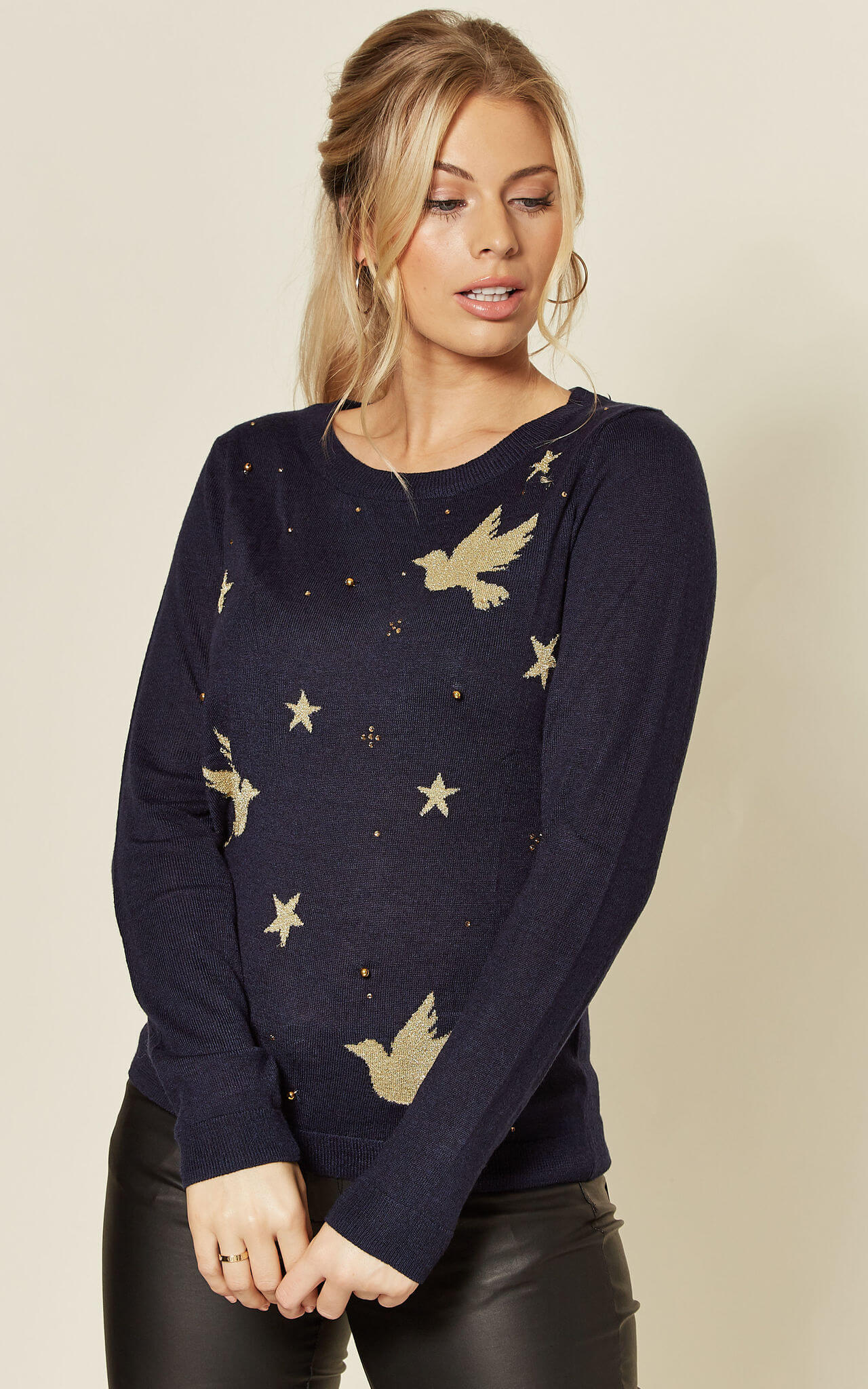 Model wears a navy jumper with gold glittery doves and bell motifs