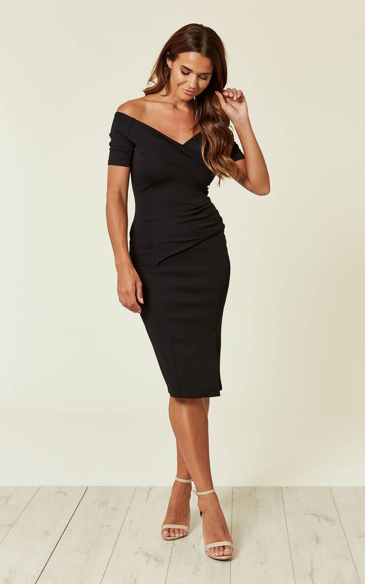 Model wears midi off shoulder bardo dress with nude heels