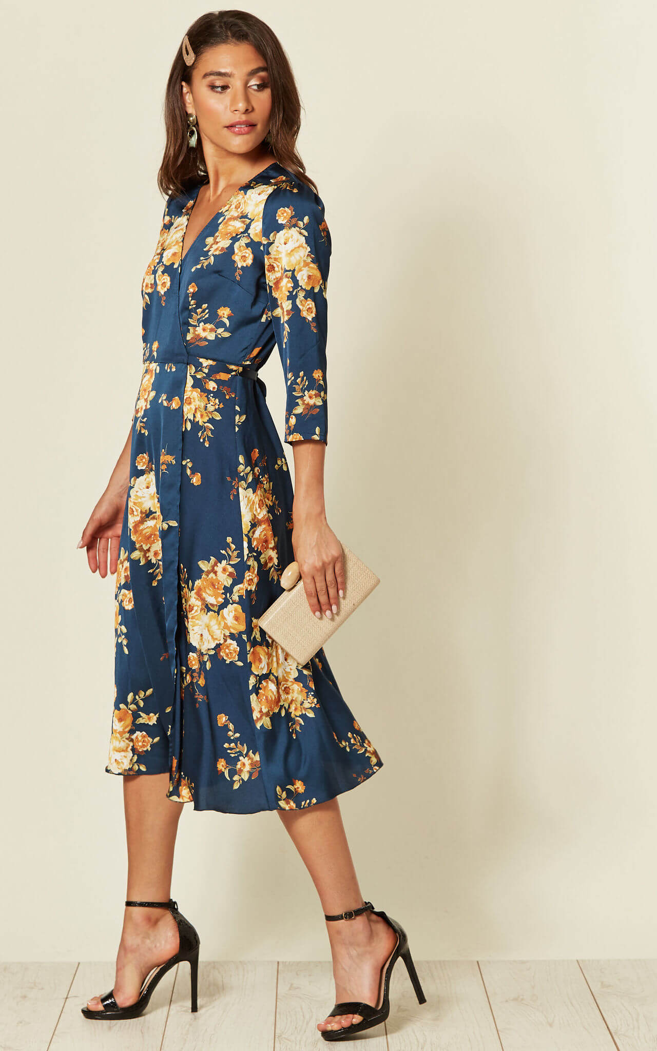 Model wears a blue wrap dress with yellow floral pattern with black heels and nude clutch bag