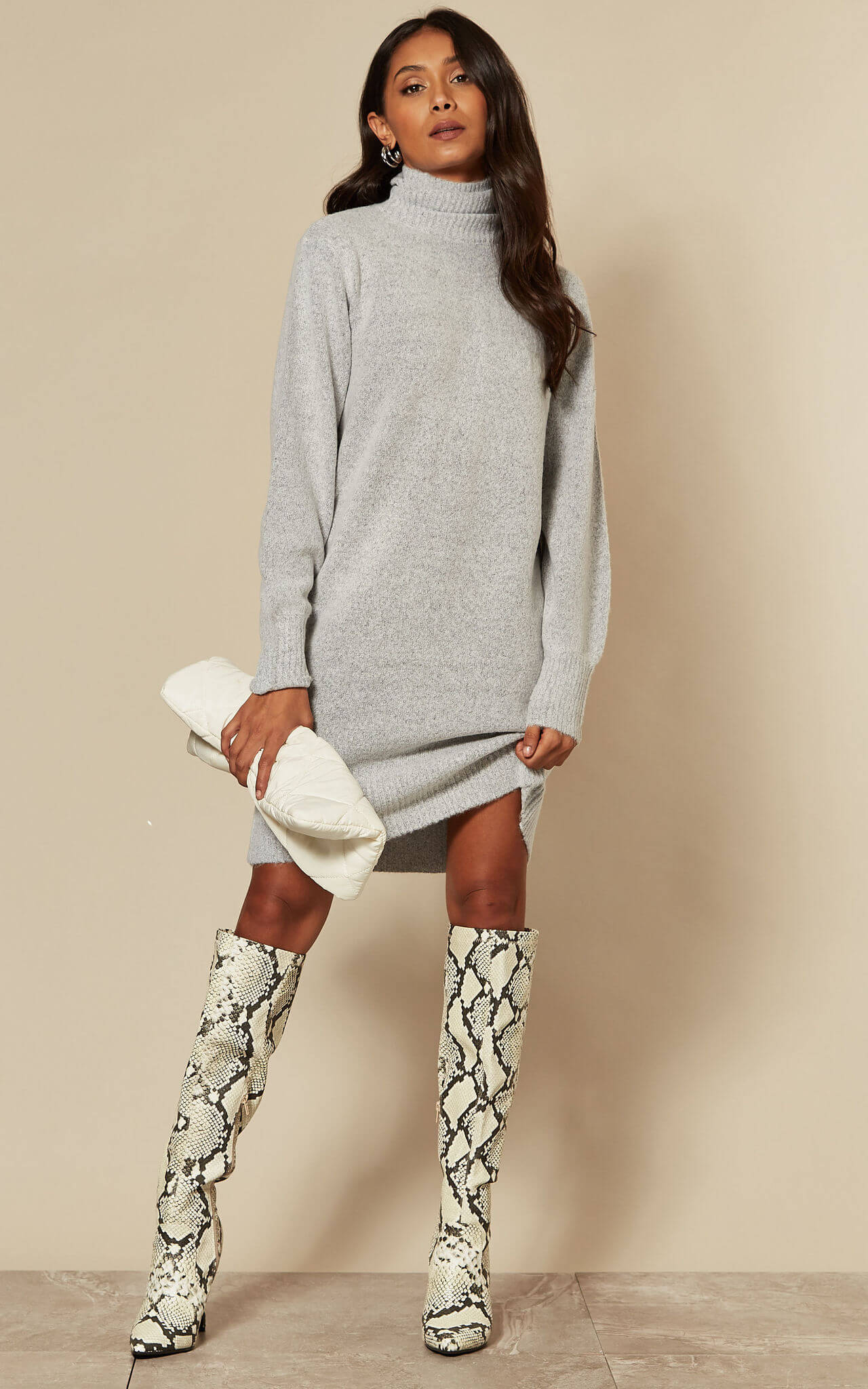 Model wears a grey roll neck jumper dress with over the knee snake print boots