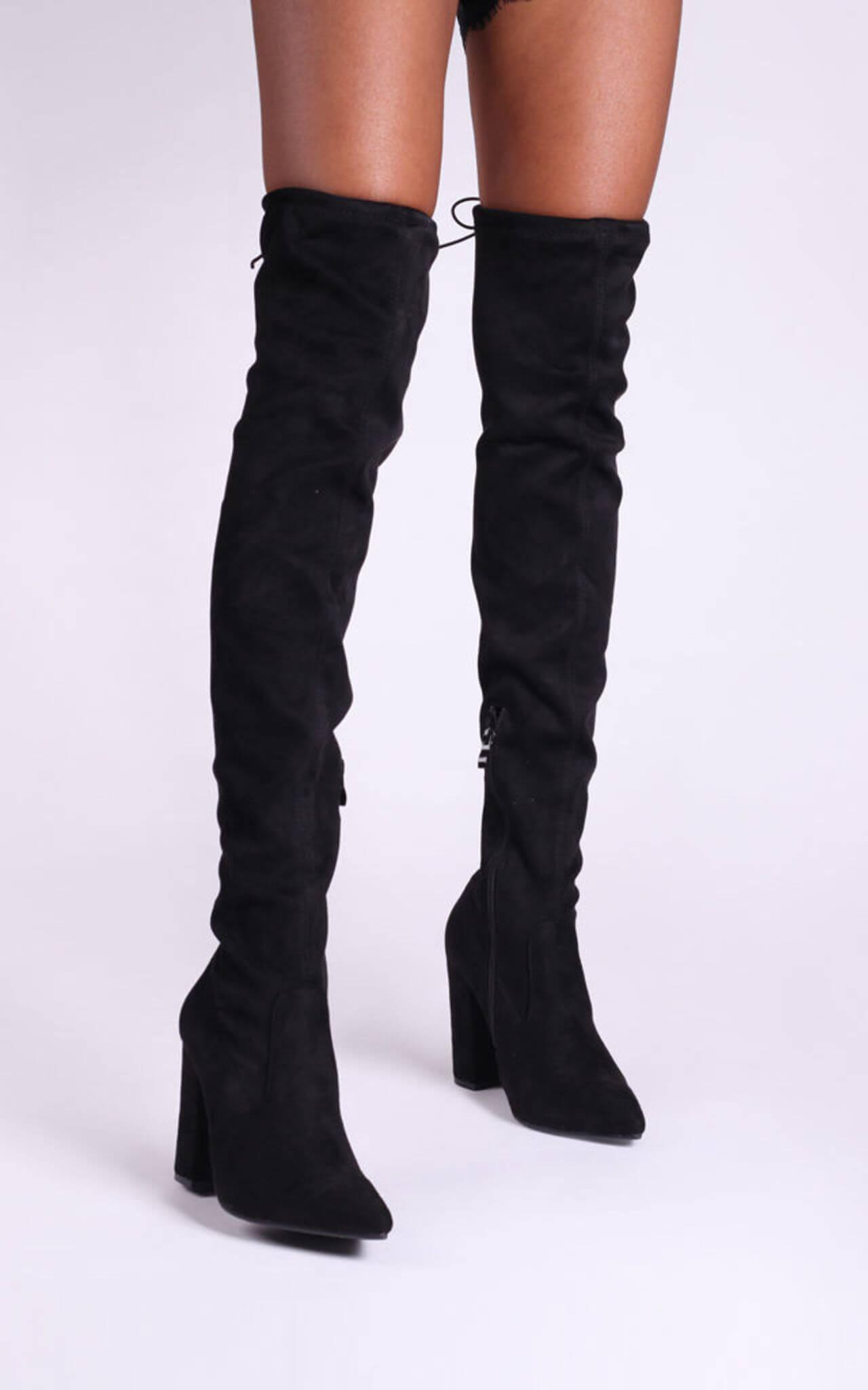 Model wears black suede over the knee boots with block heel