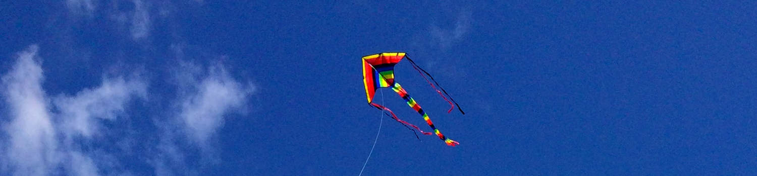 stripy kite flying in a blue sky