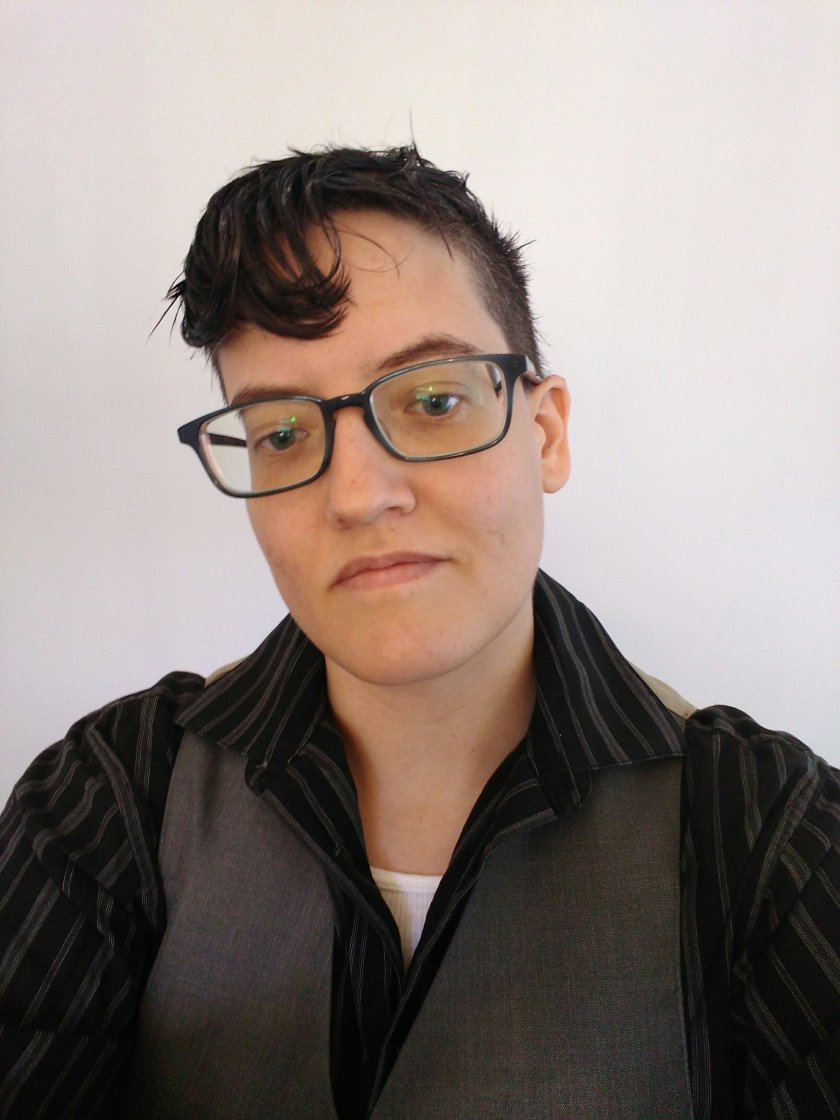 Me, an androgynous person, wearing gray square nerd glasses and a black pinstriped men's dress shirt with a grey vest. I have very dark hair in an undercut with a small pompadour with a spitcurl.