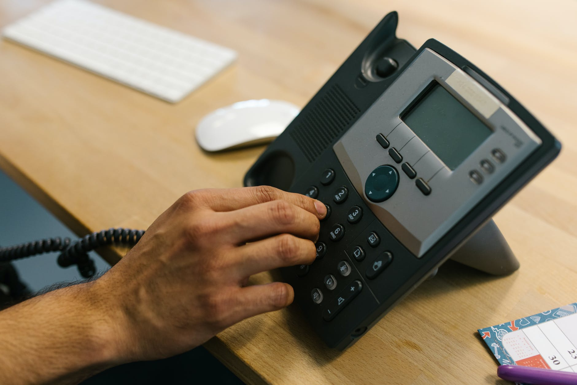 person dialing the telephone