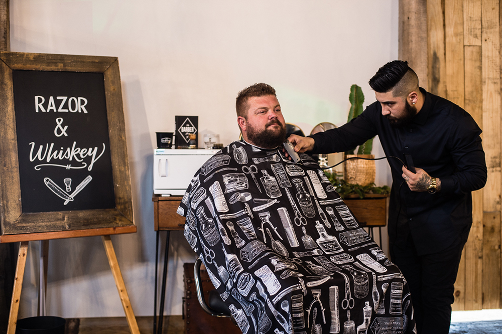 Erick trimming the gentleman's beard with all the care of an artist at Stone House Ranch