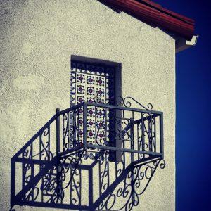 A balcony railing and the shadow of a balcony railing.