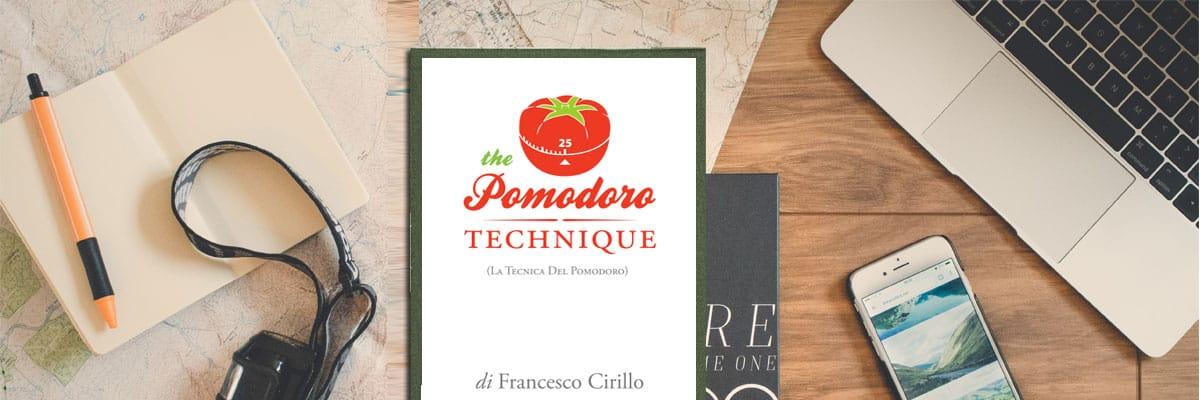 Scrivania con pc, cellulare, carta e penna e dispensa sulla Tecnica del Pomodoro