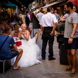 Bride in white gown sitting in pavement cafe, Venice.