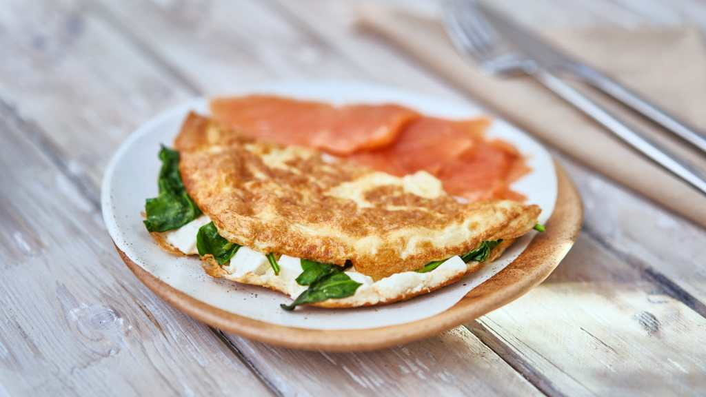 Low Carb High Fat Breakfast Meal. Omelette with Spinach, Feta Cheese, and smoked Salmon. Golden brown color. On plate, on wooden table.