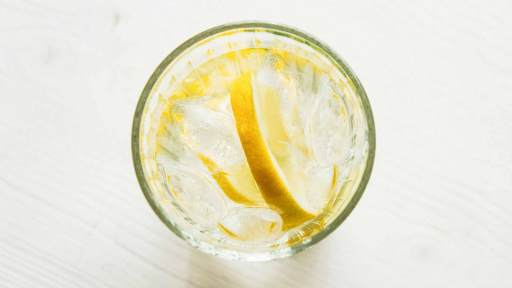 top down view of a glass tumbler with ice water and slice of lemon