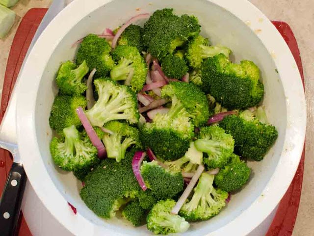 Mixing bowl with broccoli and onions tossed in olive oil