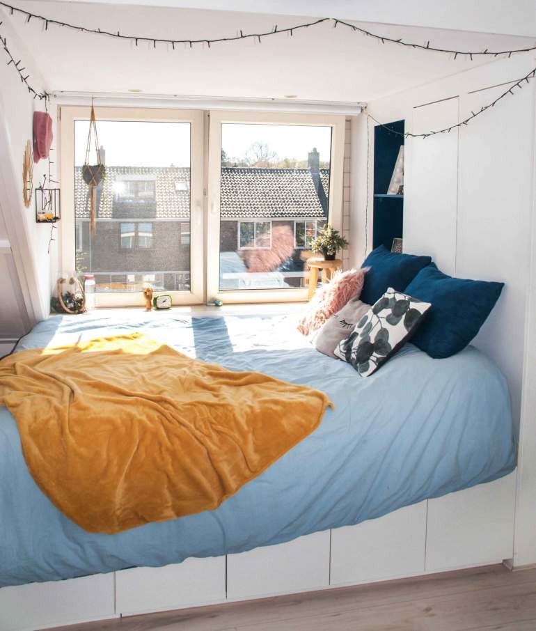 Platform bed by the window with a yellow blanket and cushions