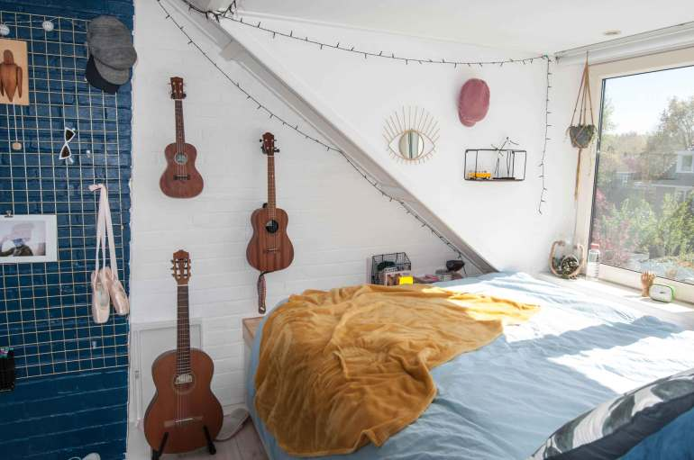 Platform bed with ukeleles on the wall