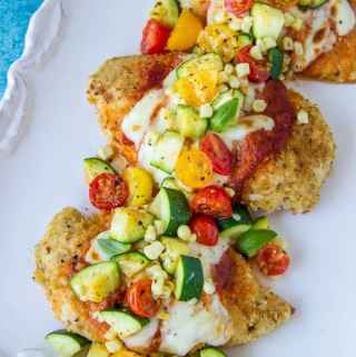 Summer Chicken Parmesan- A lightened up version of the Italian classic. Topped with fresh summer tomatoes, corn and zucchini