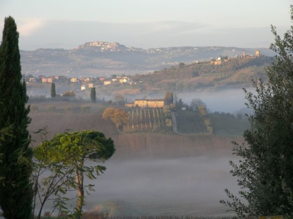 Early morning mist rises from the hills in Southern Tuscany.