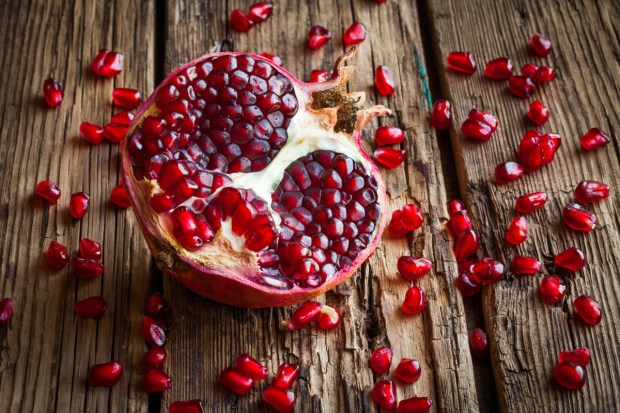Juicy pomegranate fruit over wooden vintage table