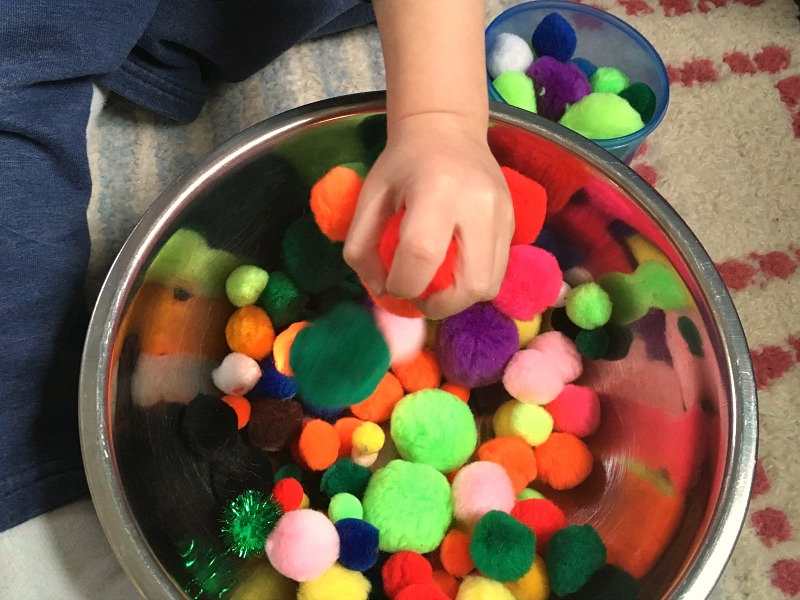 simple play idea for toddlers - set up a pompom sensory bin!