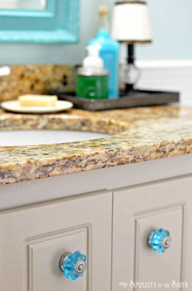 Gray bathroom cabinet with Santa Cecilia granite countertop
