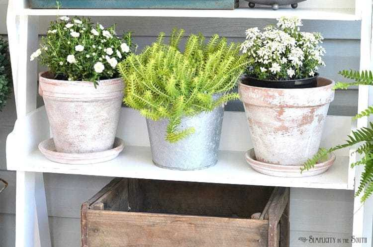 Flowers in DIY weathered pots:Need some ideas for decorating your front porch? By adding a repurposed bookshelf from inside the house, you can add plants, flowers, and even candles to welcome your guests.