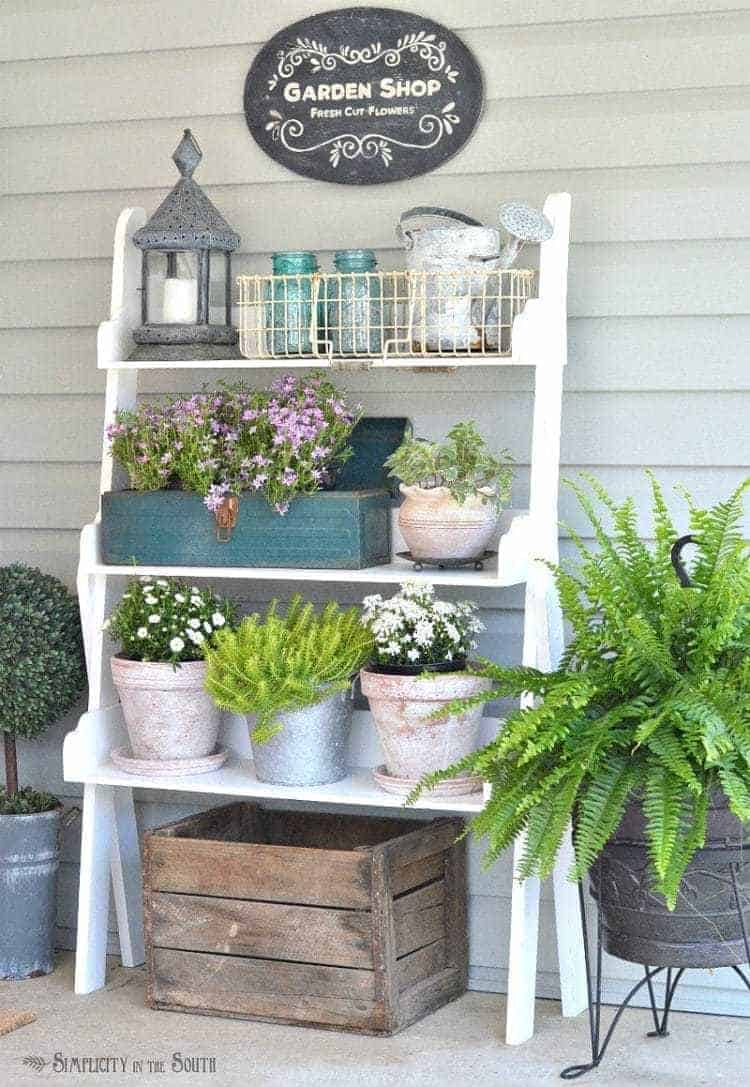 Plant shelf with potted flowers: Need some ideas for decorating your front porch? By adding a repurposed bookshelf from inside the house, you can add plants, flowers, and even candles to welcome your guests.
