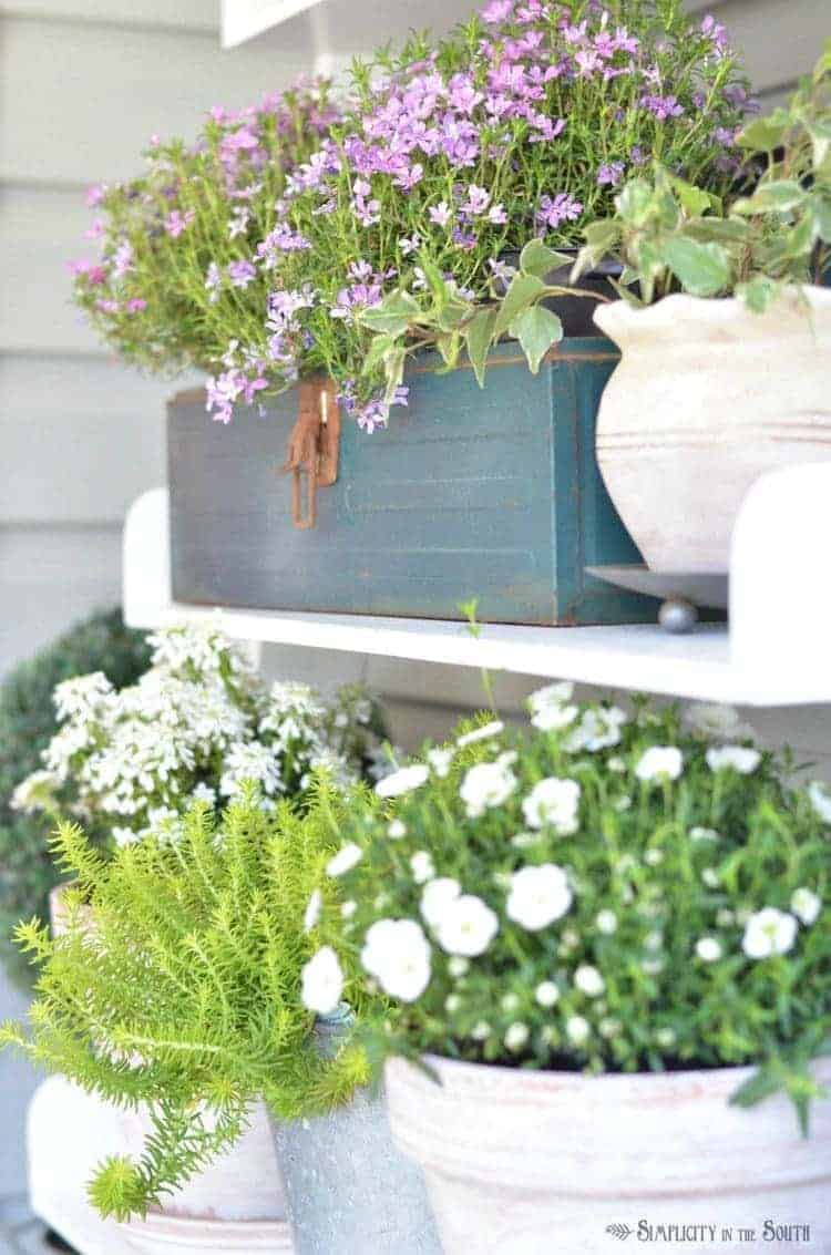 Use a repurposed vintage toolbox to hold flowers.Need some ideas for decorating your front porch? By adding a repurposed bookshelf from inside the house, you can add plants, flowers, and even candles to welcome your guests.