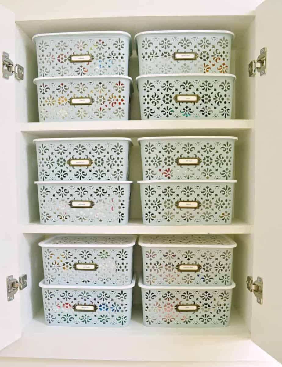 organization idea for bathroom cabinet using stacked lidded bins with labels