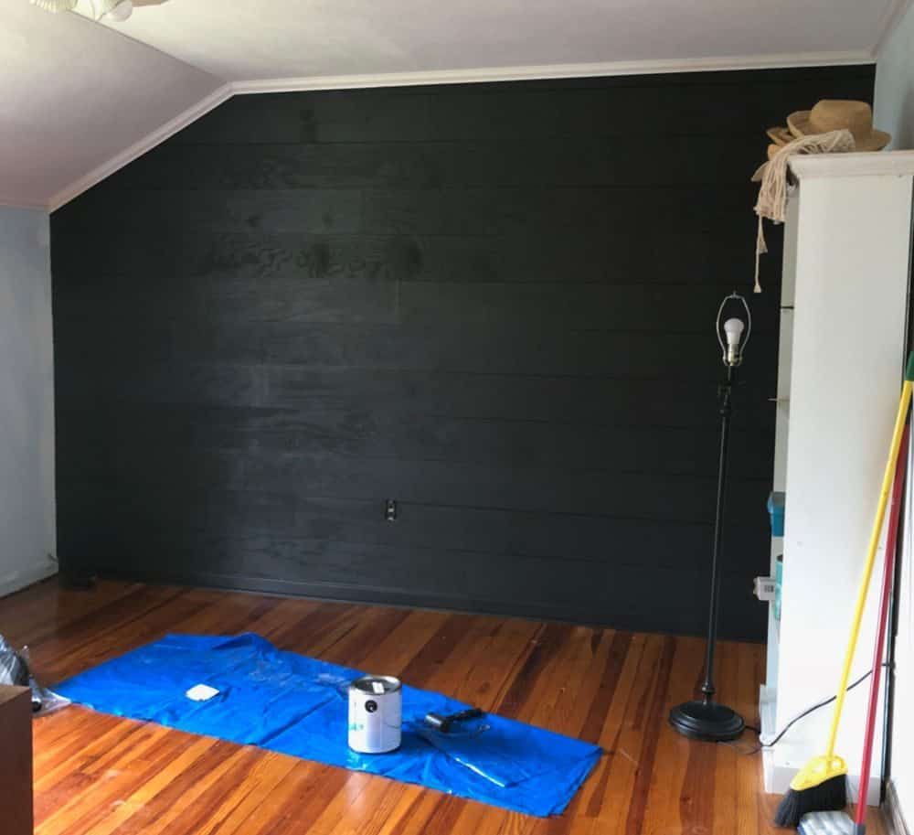 bedroom in progress with black shiplap walls
