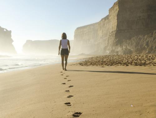 woman walking barefoot at the beach