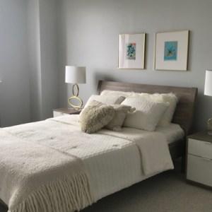 bedroom white comforter wooden headboard