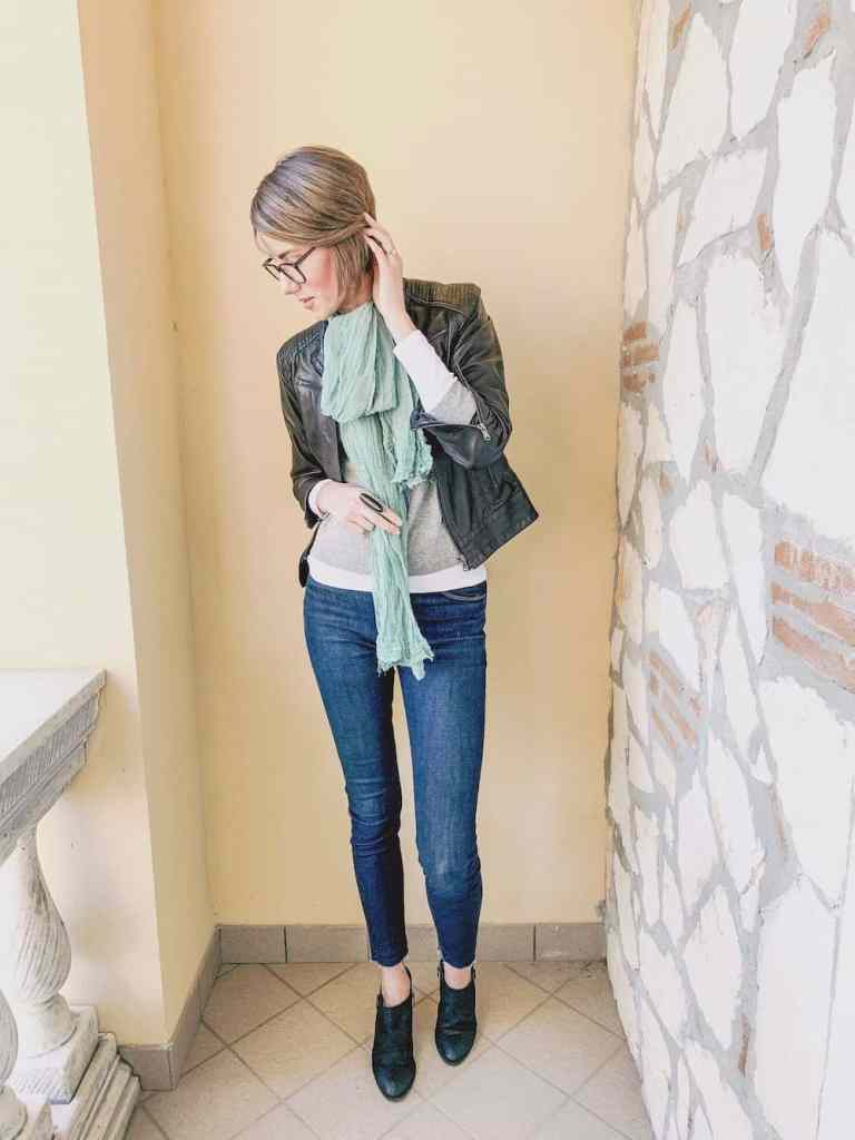 Minimalist winter outfit inspiration: a leather jacket layered over a long sleeve shirt with skinny jeans and black boots. Add a colourful scarf to bring the look together!
