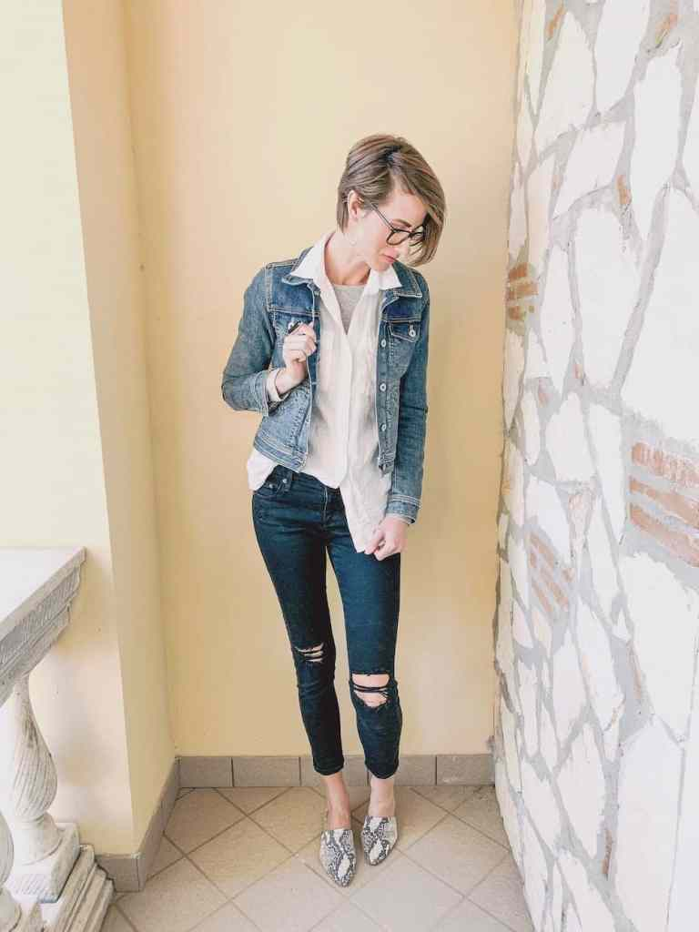 Minimalist winter outfit inspiration: a white shirt layered over a long sleeve shirt with black skinny jeans and slip on shoes. Top with a denim jacket to add warmth and interest!