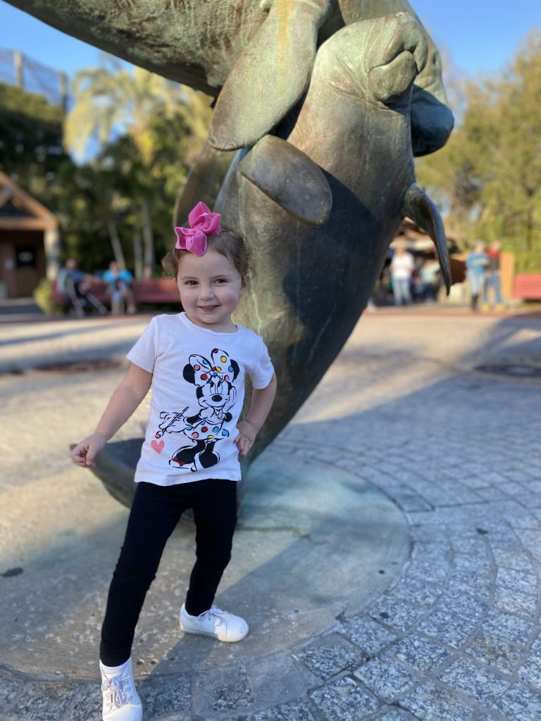 Caroline posing at the zoo by the manatees statue