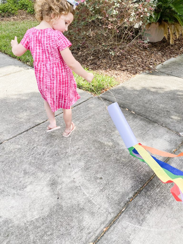 Caroline with Rainbow Windsock outside dragging it on the ground