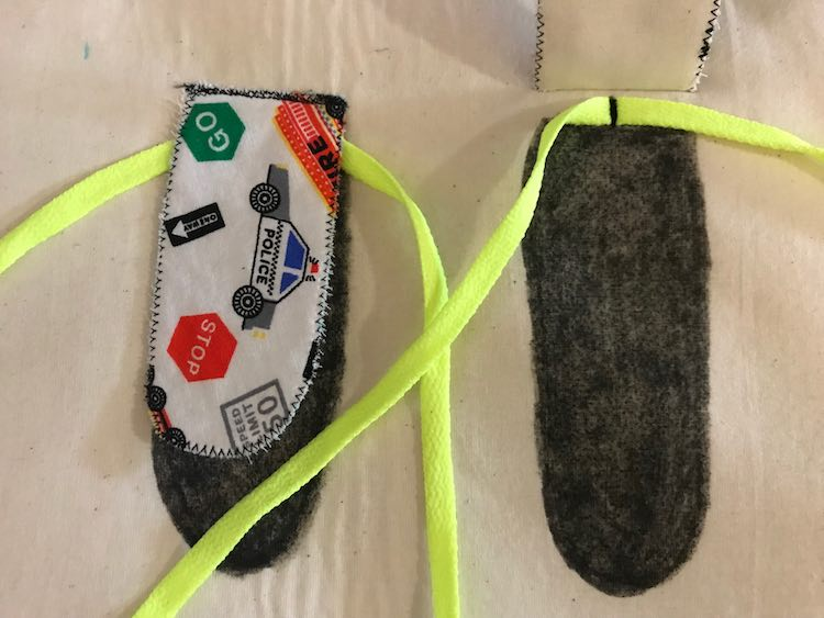 Sew the shoe lace to the center top of that black spot you colored in (right side) and then sew your tongue over top (left side). Do this on both sides.