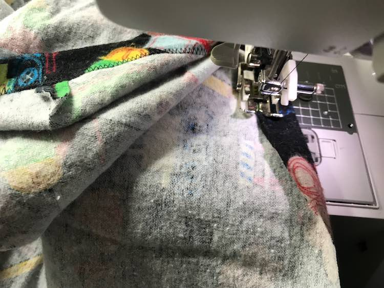 Flip the edge of the sheet over and sew along the edge. This creates a channel for the elastic so make sure it's wide enough. Also be sure to leave an open space to thread the elastic in.