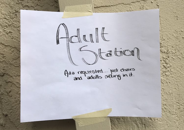 """Adult station sign: """"Adult Station - Ada requested... just chairs and adults sitting on it""""."""