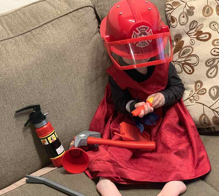 Laid out with the red dress over top of the garment and with her firetruck-related accessories to complete the look.