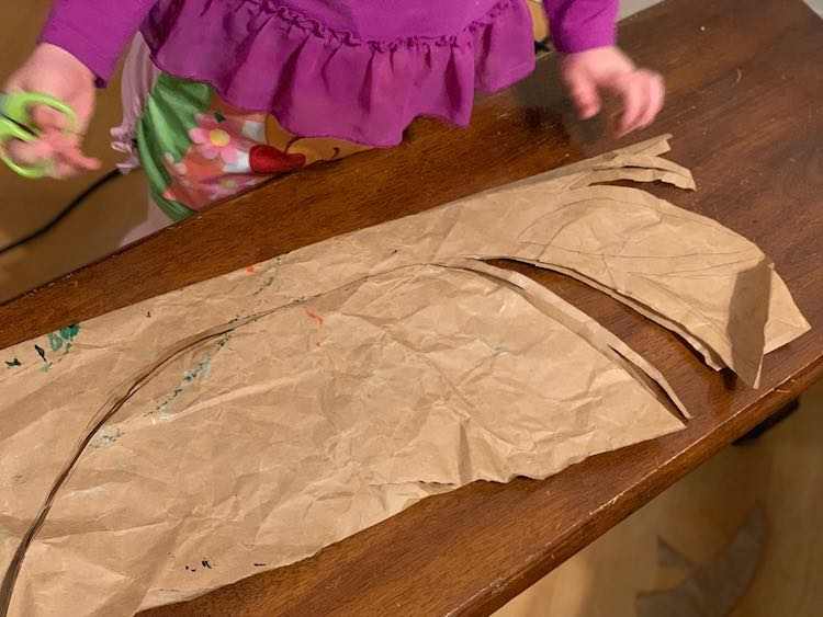 I started out by taking some brown paper, folding it in half, and quickly sketching half a tree trunk with branches on it. Make sure the tree trunk is on the side with the fold.