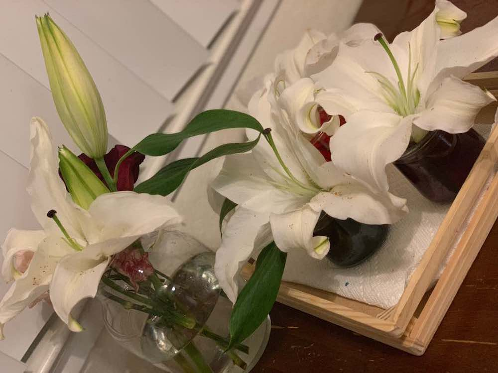 White lilies in their own respective vases.