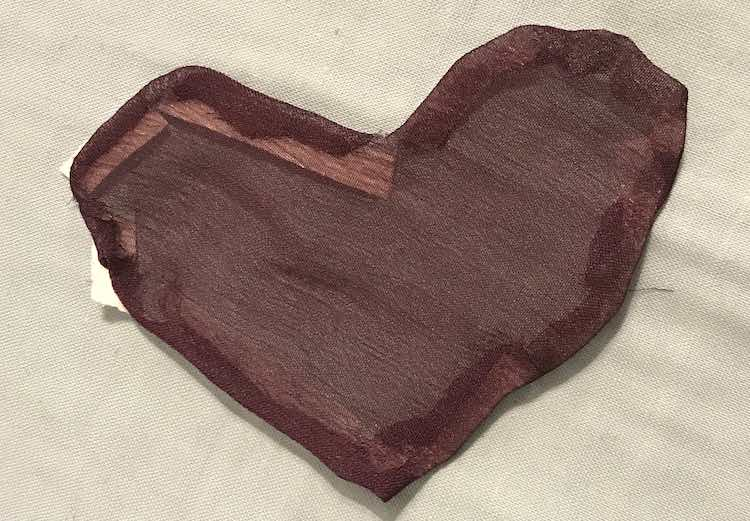 Right side of the heart shows a smoothed edge. The fabric isn't opaque so you can easily see the paper covered tape in the upper left corner along with some of the other, more transparent, tape.