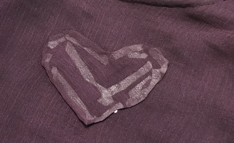 The right side of the heart shows with the rest of the camisole behind it. You aren't able to see the holes behind the heart but you can see all the tape used through the fabric.